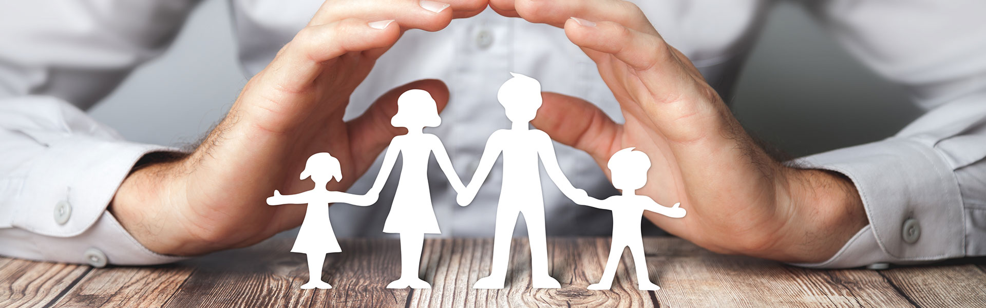 Hände formen Dach mit Papierfamilie
