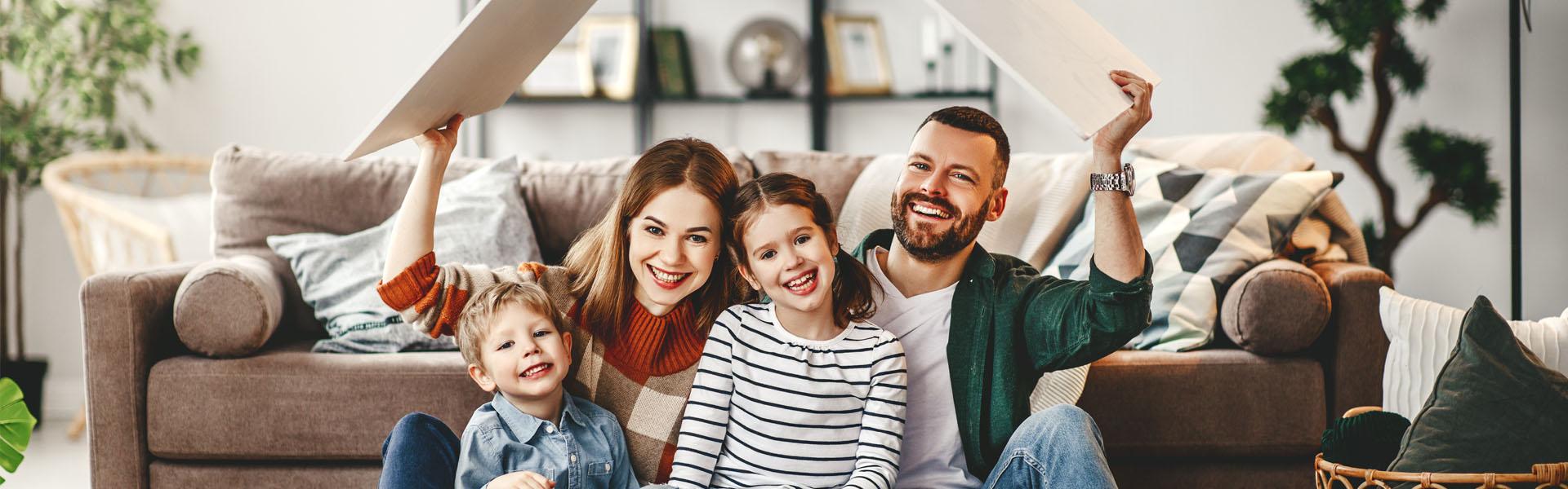 Glückliche Familie im Wohnzimmer hält sich ein Dach über dem Kopf