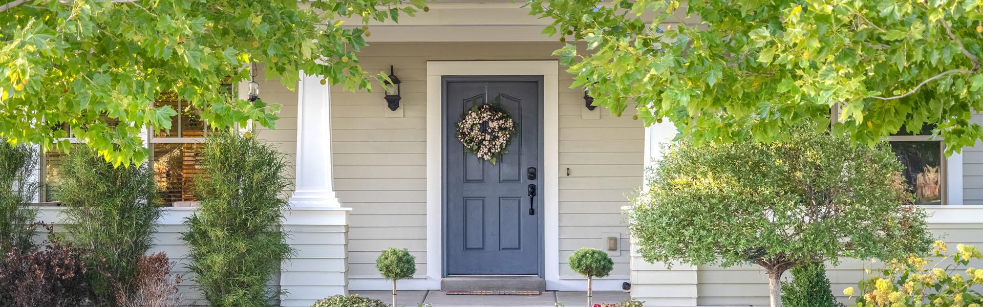 Hauseingang mit blauer Türe und Vorgarten